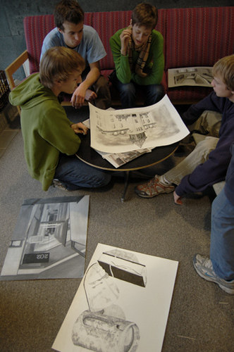 Students participate in a critique for an Observational Drawing course