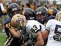 Mark Skoglund and three of his teammates bring down a Bethel University player.