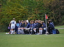 The women's soccer team watches from the sidelines.
