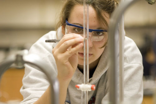 a woman wearing safety glasses conducts an experiment in a laboratory