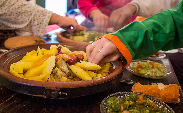 Students and family members alike dig into the tajine.