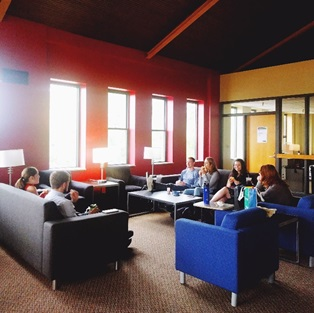 full color photo of students eating lunch together on couches