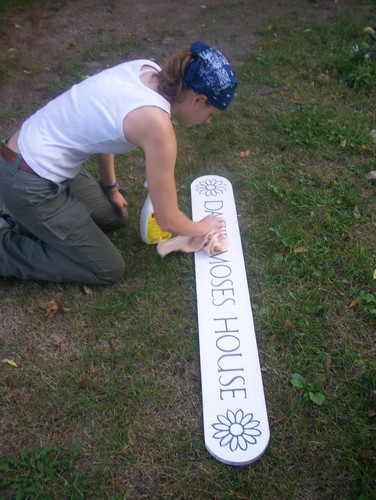Stephanie does detail work on the sign board.