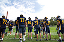 Members of the Carleton football team watch the game against Bethel University from the sidelines.