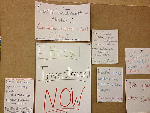 Posters urge divestment from large companies who support child labor or use fossil fuels.