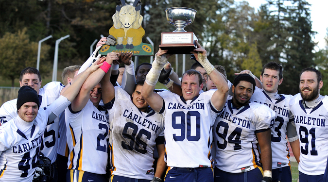 Members of the Carleton football team celebrate after winning the 'Goat' trophy.