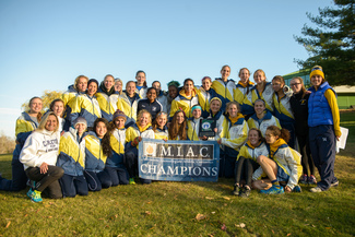 The women's cross country team celebrates a conference title at the 2014 MIAC Championship Meet