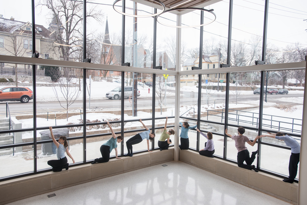 Windows become an important frame for Carleton dancers as part of a Northfield Experience routine inside the public space.