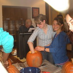 Izzy and Emily carve a pumpkin.