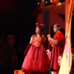 Two actors standing on stage wearing red dresses