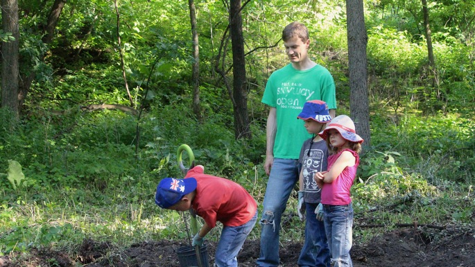 Nancy Braker leads alumni and their families in planting trees to promote the long-term ecological health of the Carleton Arboretum