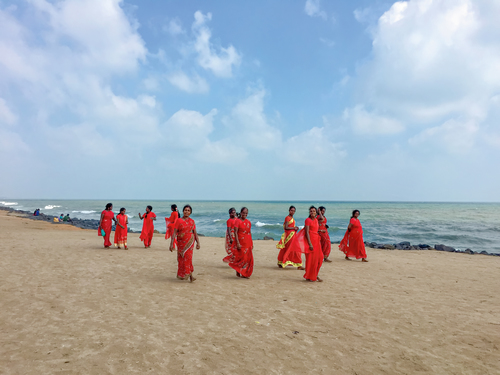 Women in red robes on a beach