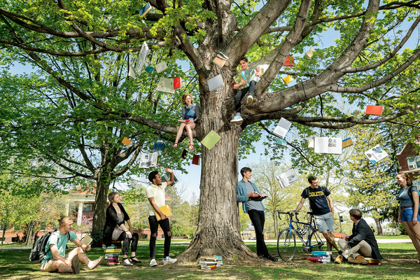 A tree filled with hanging books with students and professors gathered in and under it