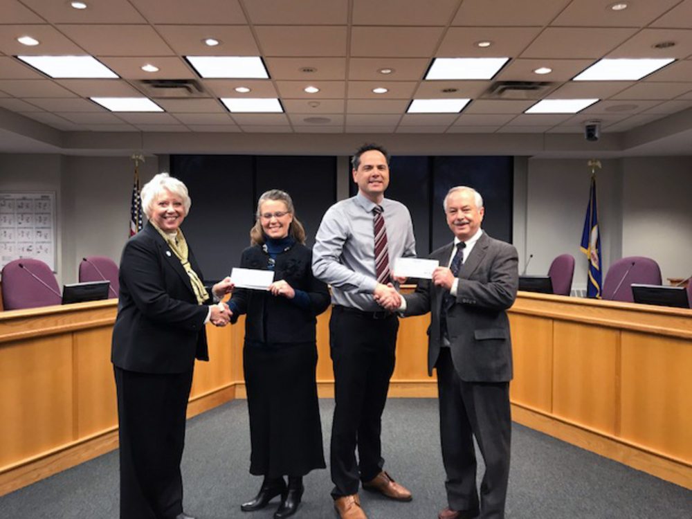 Carleton vice president and treasurer Fred Rogers (far right) and St. Olaf counterpart Janet Hanson (far left) presented the colleges' annual donation. Northfield Mayor Rhonda Pownell (middle left) and Northfield City Administrator Ben Martig (middle right) accepted the donation.