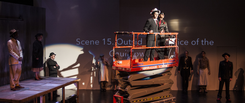 Arturo Ui, in pinstripe suit, stands in a skyjack lift onstage, addressing the audience.
