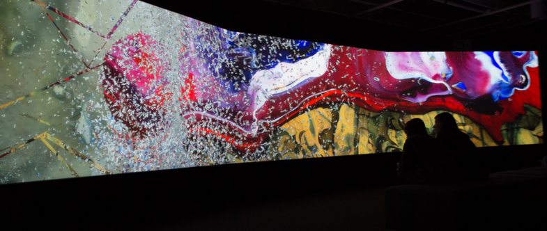 Three projection screens in a dark room displaying colorful abstract images.