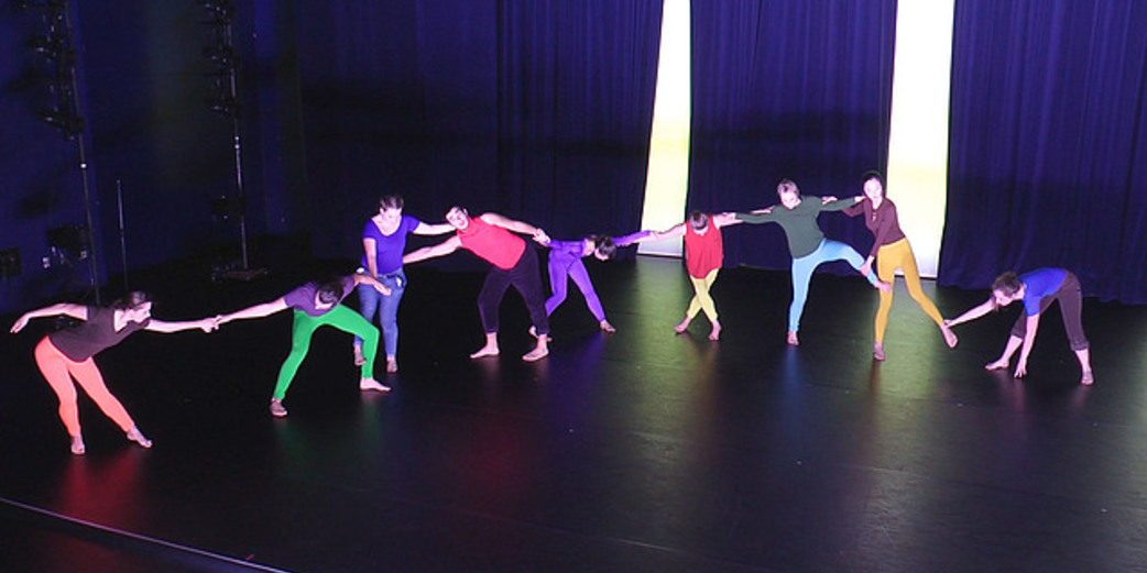 Dancers in colorful costumes make a chain across stage with their arms and legs.