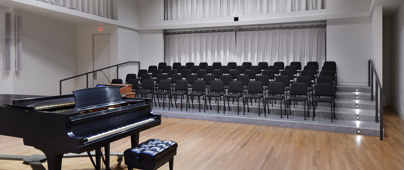 Photo of Applebaum Recital Hall, a choir rehearsal space, with piano, risers, and chairs.
