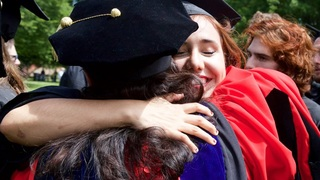 Students in graduation outfits hugging each other