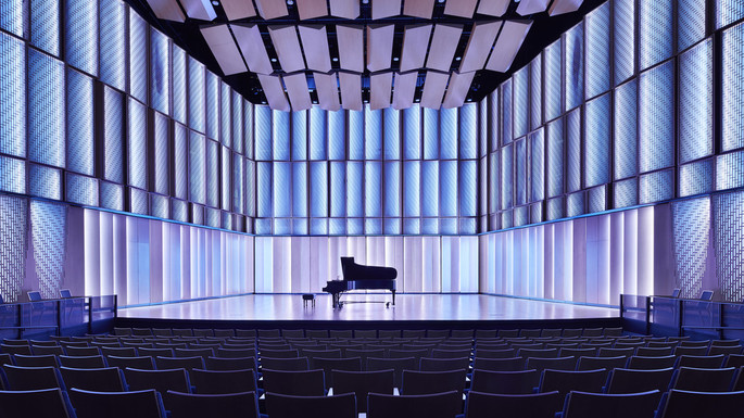 Image of Kracum Performance Hall stage, with piano and blue lighting.