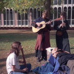 On the lawn near Olin Hall (where now stands Hulings Hall) in 1990, SCA members dance (out of frame) while Mark Heiman (guitar), Matt Cohen (Kortholt), and Michael Moore (recorder) play.