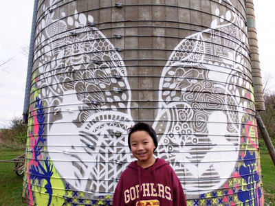 A child stands before a mural painted on a grain silo