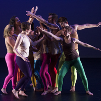 A group of dancers onstage in colorful costumes, reaching towards each other.