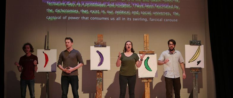 4 actors stand onstage next to easels with paintings of bananas on them.