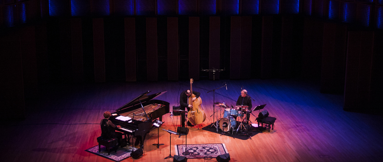 A jazz trio - piano, upright bass, and drums - on the Kracum Hall stage in pink and blue light.