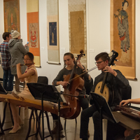Musicians play traditional Chinese instruments in front of a Chinese art gallery show.