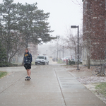 A student skateboards through an early April snow shower.