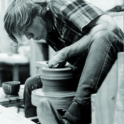 Image of a Carleton student working with clay on a potter's wheel.