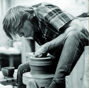A Carleton student working with clay on a potter's wheel