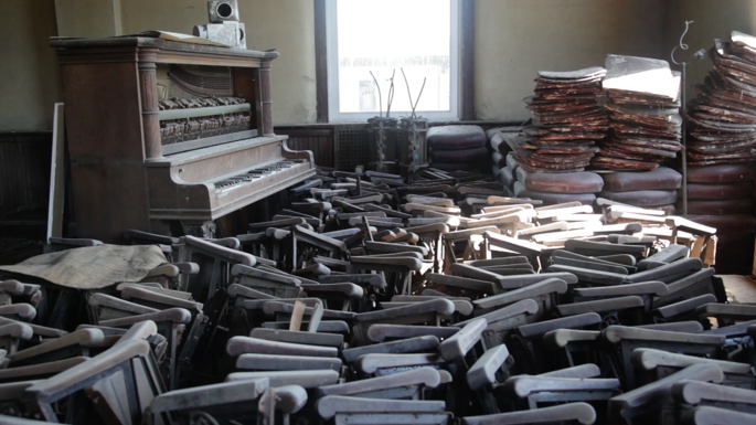 A dusty collection of miscellaneous items such as an old piano, piles of music and chair parts.