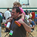 Alumnus and daughter at a pizza party in Cowling gym.