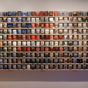 A wall of ceramic cups by artist Ehren Tool.